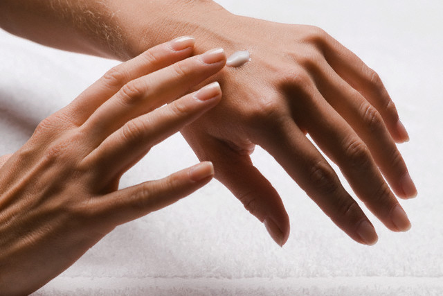 Close-up of a woman's hands applying lotion